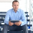 Businessman sitting on stairs with electronic tablet — Photo #52132979