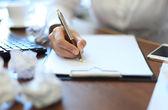 Primer plano de empresaria hace una nota en el documento empresarial — Foto de Stock