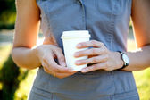Disposable cup of coffee in hand — Stock Photo
