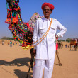Indian man standing with his decorated camel at Desert Festival, — Stock Photo #55130451