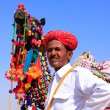 Indian man standing with his decorated camel at Desert Festival, — Stock Photo #55549885