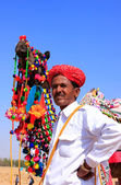 Indian man standing with his decorated camel at Desert Festival, — Stock Photo