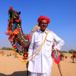 Indian man standing with his decorated camel at Desert Festival, — Stock Photo #55845239