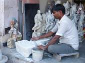 Man working on a statue at a workshop in Delhi, India — Stock Photo