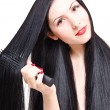 Portrait of a beautiful young woman combing her long groomed hair — Stock Photo #71313017