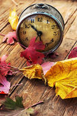 Old clock on the background of fallen leaves — Stock Photo