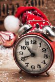 Old-fashioned alarm clock and red Christmas cap — Stock Photo