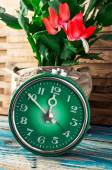 Symbol of spring green clock and blossoming flower — Stock Photo