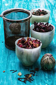 Variety of dry tea leaves in jade stacks on wooden background — Foto de Stock