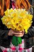 Figure girl with bouquet of daffodils in his hands — Foto Stock