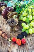 Vattenpipa mitt i klasar av druvor och jordgubbar — Stockfoto