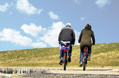 A couple cycling on a causeway in Zeeland — Stock Photo