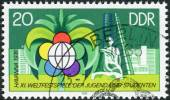 Postage stamp printed in Germany (GDR), dedicated to 11th World Youth Festival, Havana, shows Festival Emblem and New Buildings — Foto Stock