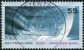 Postage stamp printed in Germany, dedicated to the Bible Year, shows a hand and an open Bible — Stock Photo