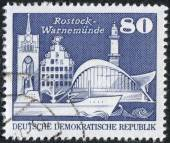 Postage stamp printed in Germany, shows attractions Kroepeliner Tor, Sonne Haus in Rostock, and Teepott and lighthouse in Warnemuende — Stock Photo