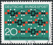 Postage stamp printed in Germany, dedicated to the 125th anniversary of Synthetic textile fiber research, shows a cloth pattern formed of chain molecules — Foto Stock