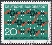 Postage stamp printed in Germany, dedicated to the 125th anniversary of Synthetic textile fiber research, shows a cloth pattern formed of chain molecules — Stockfoto