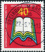 Postage stamp printed in Germany, dedicated to the International Book Year, depicts an open book — Foto Stock
