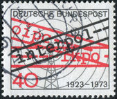 "Postage stamp printed in Germany, dedicated to the 50th anniversary of International Criminal Police Organization, shows the Radio Tower and the inscription ""Interpol"" — Stockfoto"