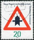 "Postage stamp printed in Germany, dedicated to New traffic rules, shows a road sign ""Proceed with caution"" — 图库照片"