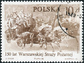Postage stamp printed in Poland, dedicated to the 150th anniversary of the Warsaw Fire Brigade, shows The Fire Brigade on the Cracow Outskirts on Their Way to a Fire, 1871, by Josef Brodowski — Stockfoto