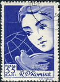 Postage stamp printed in Romania, dedicated to the 50th anniversary of International Women's Day, shows Woman's face, peace dove and globe — Foto Stock