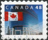 Postage stamp printed in Canada, shows Flag and Canada Post Headquarters, Ottawa — Stock Photo
