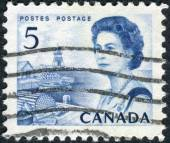 Postage stamp printed in Canada, shows a fishing village on the Atlantic coast, a portrait of Queen Elizabeth II — ストック写真