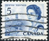 Postage stamp printed in Canada, shows a fishing village on the Atlantic coast, a portrait of Queen Elizabeth II — Stock Photo