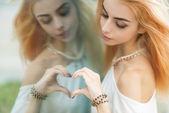 Young beautiful woman making a heart shape. — Stock Photo