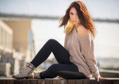 Mladá žena v sezení na dřevěné desce. — Stock fotografie