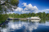 Boats at dock on a lake with blue sky — Stock Photo