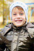Four year boy in Autumn park wearing a warm hat — Stock Photo