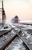Passenger train rapidly moving along the snow track — Stock Photo