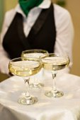 Three glasses of Champagne and a waiter — Stock Photo