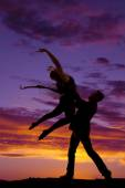 Silhouette couple dancing he lift her arms up — Stock Photo