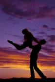 Silhouette couple dancing he lifts her up — Stock Photo