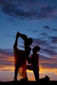 Silhouette couple dancing scorpion kneel — Stock Photo