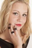 Black rings on fingers by chin — Stock Photo