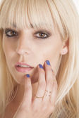 Woman with rings on fingers by face — Stock Photo
