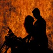 Silhouette couple kiss on motorcycle fire — Stock Photo #53048873