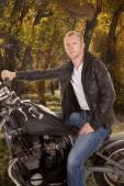 Man in black jacket motorcycle one hand on handlebars looking tr — Stock Photo