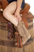 Cowgirl on saddle on barrel — Stock Photo