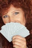 Woman red hair look over fan of cards smile — Stock Photo