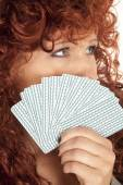 Woman red hair look over fan of cards to the side — Stock Photo