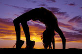 Silhouette of woman doing back bend — Stock Photo