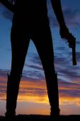Silhouette of woman holding a gun — Stock Photo