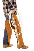 Cowboy legs chaps hold rope — Stock Photo