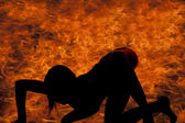 Woman silhouette in fire crawling — Stock Photo