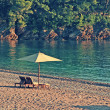 Two deck chairs and umbrella on the beach in rocky bay. — Stock Photo #51893641